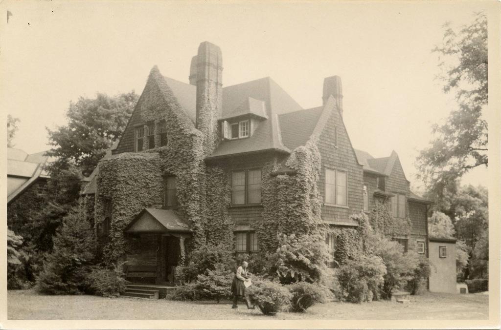 La imagen es una foto de la casa, tomada en 1902. Frente a la casa va pasando un hombre en mangas de camisa, llevando al brazo su chaqueta y con unos papeles en la mano.
