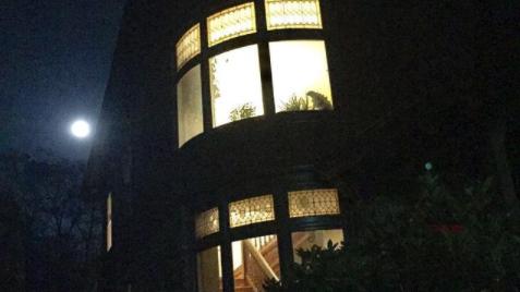 La foto muestra la silueta de la casa en una noche de luna llena; las luces están encendidas y se ve la escalera de madera. En el ventanal curvo se ve la figura de Godzilla entre las plantas.